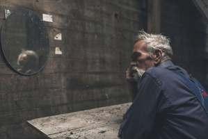 Thoughtful Senior Man Sitting Inside a Farmhouse