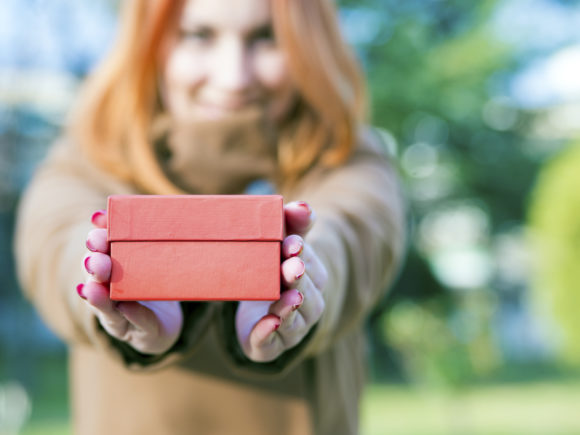 Woman holding a red gift box  a gesture of giving