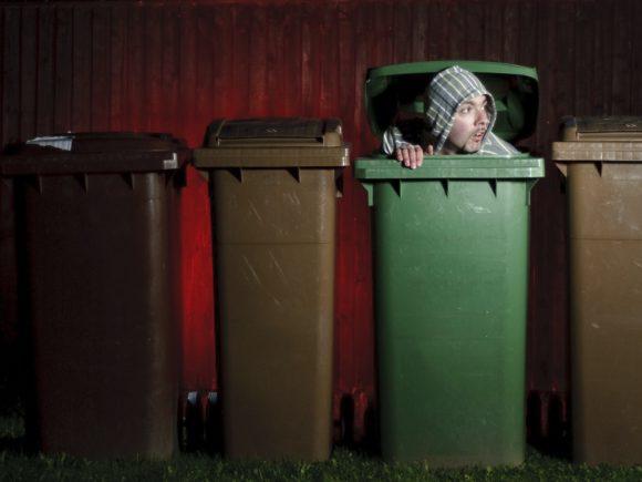 Man hiding in garbage bin.