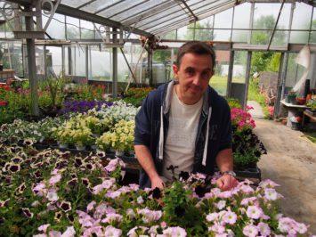 Jean Dubois derrière des fleurs.